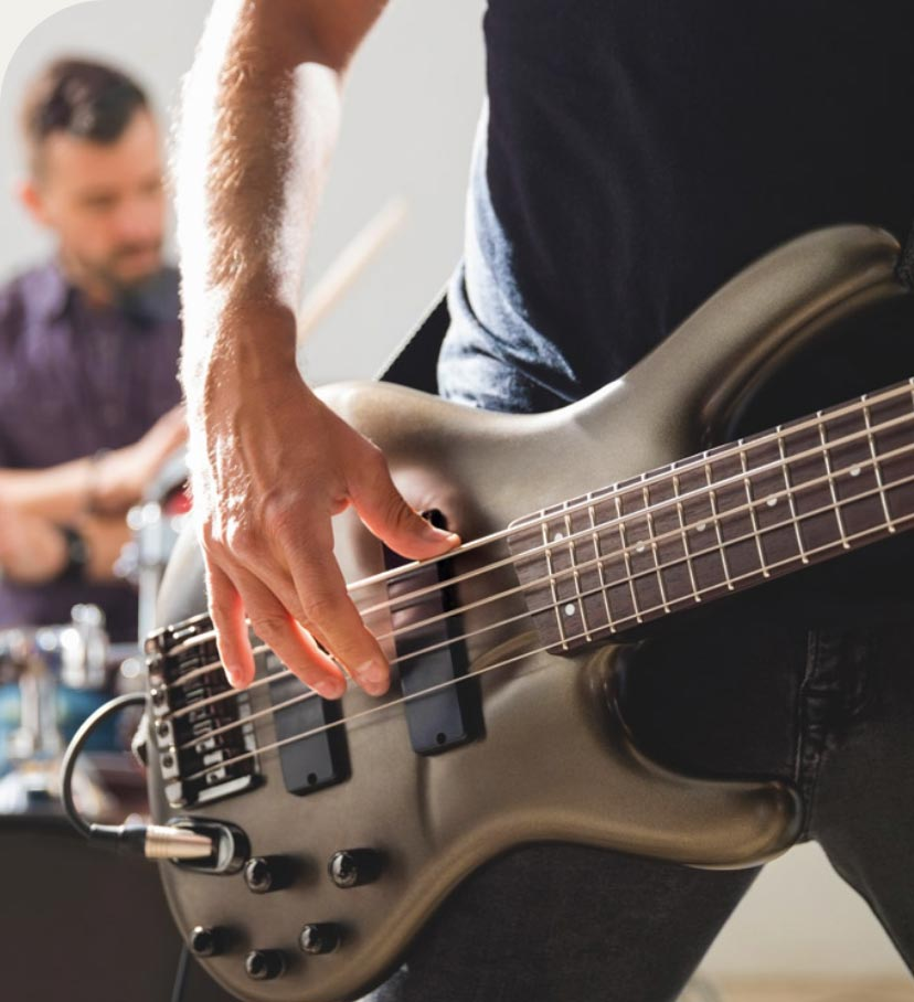 Guy playing a bass guitar with a guy playing drums in the background.